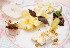 Cheese plate with fruits and nuts Stock Photos