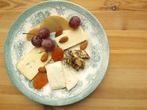 Cheese plate with fruits and nuts. Cheese plate. Five sorts of cheese. Cheddar, Talegio, Cheddar, aged in porter, Scamorza and cheese with blue mold Stock Photo