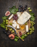 Cheese plate with gorgonzola and Camembert cheese with Knife for cheese white and dark grapes, honey and jam on a wooden cutting. Cheese plate with gorgonzola stock photos