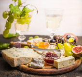 Cheese plate with Gorgonzola and Camembert with honey and jam dark and bright grapes glass of wine grapes on a branch inside on da Stock Image