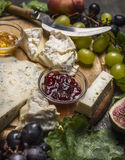 Cheese plate with gorgonzola,Camembert jam and honey,grapes ,peach on wooden cutting board close up Royalty Free Stock Photos