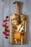 Cheese plate: Gouda cheese, green grapes and red autumn leaves Stock Photo