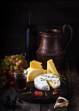Cheese plate,grape and wine. Still life in rustic style. Old dark wooden background, selective focus Royalty Free Stock Photography