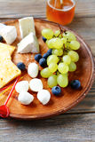 Cheese plate with grapes Stock Image