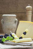 Cheese Plate with Grapes. And Gouda Cheese skewers at rustic italian ambience Royalty Free Stock Photography