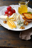 Cheese plate with grapes, honey, bread and walnuts on old wooden table Royalty Free Stock Images