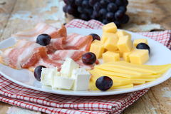 Cheese plate with grapes  and smoked bacon Royalty Free Stock Photography