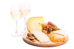 Cheese plate with grapes and white wine. Cheese board with grapes and white wine isolated on white background. Variety of soft and hard cheeses stock photos
