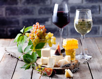 Cheese plate with honey, grape, wine in glasses. Cheese plate with honey, nuts and grape and white and red wine in glasses on a wooden backround Royalty Free Stock Photos