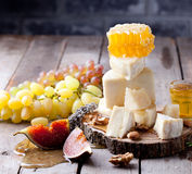 Cheese plate with honey, grape, wine in glasses Stock Images