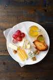 Cheese plate with honey, grapes, bread and walnuts on old wooden background Stock Photo