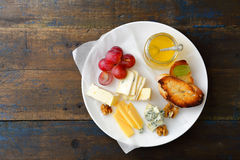 Cheese plate with honey, grapes, bread and walnuts on old wooden board Stock Photo