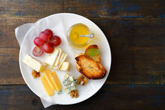 Cheese plate with honey, grapes, bread and walnuts on old wooden table Royalty Free Stock Photos