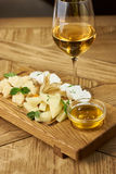 Cheese plate with honey and wine Stock Images