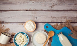 Cheese on plate and milk bottle on wooden rustic background. Healthy eating concept background. View from above. Stock Photos