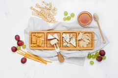 Cheese plate near grapes, honey and cracker on white marble background. Various types of cheese on wooden plate near grapes, honey and cracker on white marble stock image