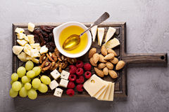 Cheese plate with nuts, honey and grapes Stock Image