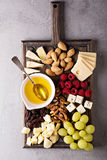 Cheese plate with nuts, honey and grapes Stock Photos