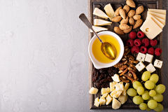 Cheese plate with nuts, honey and grapes Stock Images