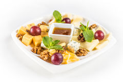 Cheese Plate with nuts and honey. On white plate Stock Photography
