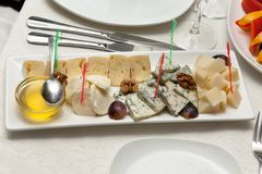 Cheese plate on restaurant table. Cheese plate with honey on restaurant table Royalty Free Stock Image