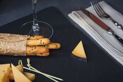 Cheese plate served with crackers and glass of white wine on dar Stock Images