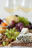 Cheese plate served with grapes, jam, cured melon, crackers and Stock Images