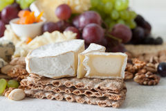 Cheese plate served with grapes, jam, cured melon, crackers and Royalty Free Stock Photos