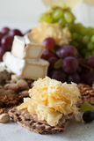 Cheese plate served with grapes, jam, cured melon, crackers and Stock Photos