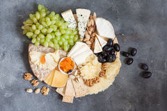 Cheese plate served with grapes, jam, cured melon, crackers and Royalty Free Stock Images