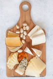 Cheese plate served with grapes, jam, cured melon, crackers and Stock Photography