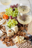 Cheese plate served with grapes, jam, cured melon, crackers and Royalty Free Stock Photography