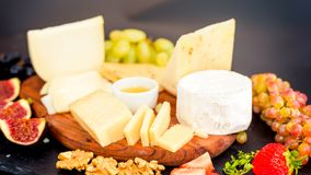 Cheese plate served with grapes, jam, figs stock image