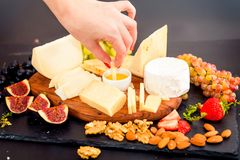 Cheese plate served with grapes, jam, figs Royalty Free Stock Image