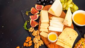 Cheese plate served with grapes, jam, figs stock photo