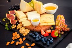 Cheese plate served with grapes, jam, figs royalty free stock photography