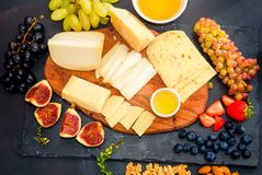 Cheese plate served with grapes, jam, figs. Crackers and nuts royalty free stock image