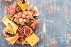Cheese plate served with grapes, jam, figs, crackers and nuts on a background. royalty free stock images