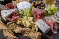 Cheese plate served with grapes, jam, prosciutto and crackers Stock Photos
