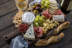 Cheese plate served with grapes, jam, prosciutto and crackers Stock Photo