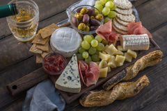 Cheese plate served with grapes, jam, prosciutto and crackers Royalty Free Stock Images