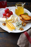 Cheese plate served with honey, grapes, bread, walnuts and wine on old wooden table Stock Image