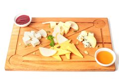 Cheese plate served with pumpkin seeds, jam, honey and green mint. Top view. Assorted cheeses Camembert, Brie, Parmesan blue chees royalty free stock images