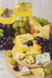 Cheese plate served with wine, fresh grapes and pears Stock Photography
