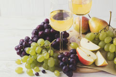 Cheese plate served with wine, fresh grapes and pears Royalty Free Stock Photos