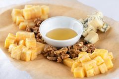 Cheese plate served with walnuts and honey royalty free stock photography
