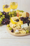 Cheese plate served with wine, fresh grapes and pears Stock Image