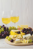 Cheese plate served with wine, fresh grapes and pears Royalty Free Stock Photo