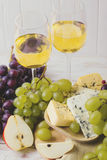 Cheese plate served with wine, fresh grapes and pears Stock Images