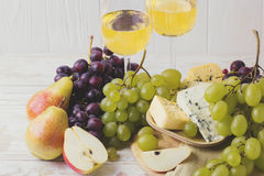Cheese plate served with wine, fresh grapes and pears Royalty Free Stock Images